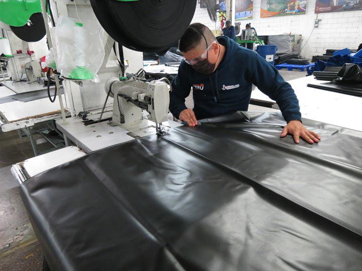 Hombre utilizando maquina de coser industrial para costura de una lona.